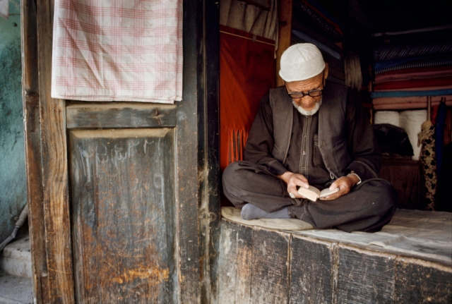 01795_16, Afghanistan, 08/1992, AFGHN-14041. A man in a white hat reads from a small book. Retouched_Ekaterina Savtsova 08/30/2014