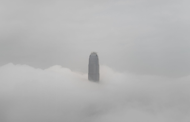 The IFC tower is seen shrouded in fog in Hong Kong on March 16, 2015. The foggy weather in the Southern Chinese city is caused by a humid maritime airstream affecting the south China coastal areas. AFP PHOTO / Philippe Lopez (Photo credit should read PHILIPPE LOPEZ/AFP/Getty Images)