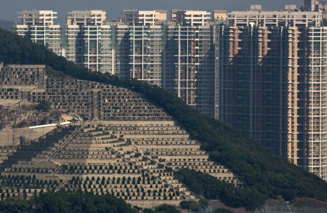 In this Nov. 22, 2015 photo, graves cover a hillside in front of apartment buildings in Hong Kong,the cramped southern Chinese city of 7.2 million. In tightly-packed Hong Kong, the dead are causing a problem Limited land to build on and soaring property prices mean Hong Kong is fast running out of space to store the dead. for the living. (AP Photo/Kin Cheung)