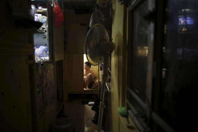 "Akee, 34, who works as a waiter rests in a wooden box that he lives in Hong Kong October 9, 2012. In Hong Kong's middle-class residential area, short distance from its shopping and financial districts, 24 people live in these wooden boxes, or ""coffin homes"", packed in a single apartment of little over 50 square meters. Its residents pay 1450 Hong Kong dollars ($180) for their living space built of wooden panels of 2 meters by 70 cm. To maximize income from the rent in central Hong Kong landlords build ""coffin homes"", nicknamed due to their resemblance to real coffins. Space has always been at a premium in Hong Kong where developers plant high-rises on every available inch. REUTERS/Damir Sagolj (CHINA - Tags: SOCIETY REAL ESTATE BUSINESS) - RTR38YAK"