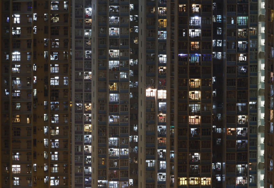 "In this Dec. 1, 2015 photo, an apartment building is seen in Hong Kong where both the living and the dead compete for space in the densely populated southern Chinese city. Limited land to build on and soaring property prices mean Hong Kong is fast running out of space to store the dead. That's a problem for residents who visit grave sites on ""tomb sweeping"" holidays to burn incense and pay respects to venerated dead ancestors as prescribed by Chinese tradition. (AP Photo/Kin Cheung)"