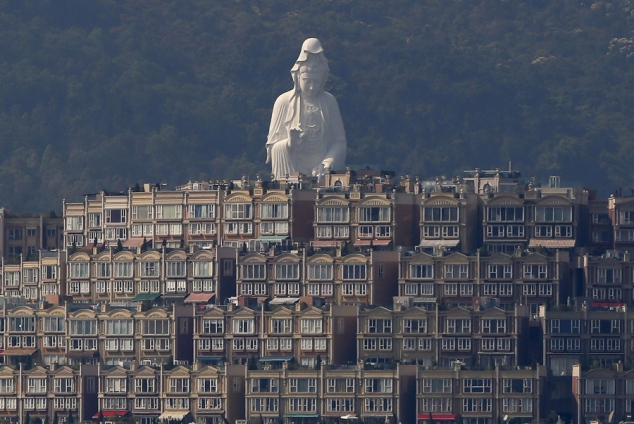A 76-meter-high (249-feet) bronze-forged white Buddhist Avalokitesvara or Guan Yin statue, part of the Tsz Shan Monastery, stands behind luxurious houses at Taipo district in Hong Kong April 16, 2015. The monastery, officially opened to the public by reservation on April 15, 2015, received contribution of HK$1.7 billion ($219 million) from Hong Kong tycoon Li Ka-shing's personal foundation to cover the construction and daily operating costs, according to the monastery. REUTERS/Bobby Yip - RTR4XJYT