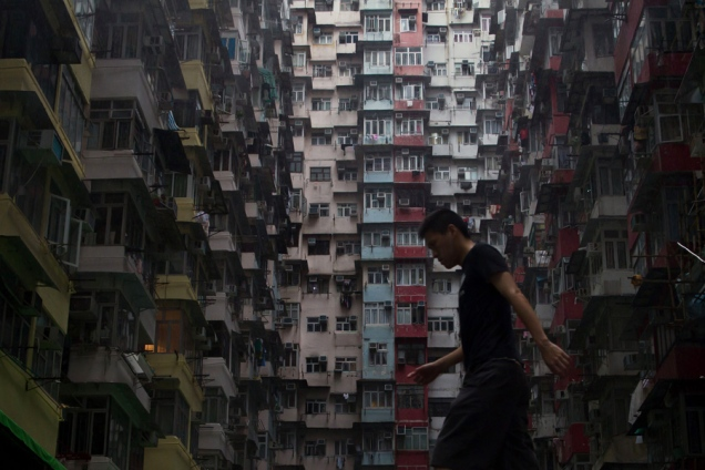 A man walks before a residential apartments in Hong Kong on May 16, 2015. AFP PHOTO / DALE DE LA REY (Photo credit should read DALE de la REY/AFP/Getty Images)