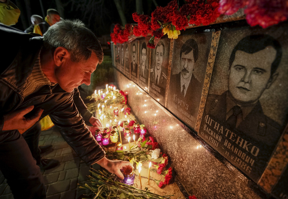 A man lights candles at a memorial, dedicated to firefighters and workers who died after the Chernobyl nuclear disaster, during a night service near the Chernobyl plant in the city of Slavutych